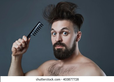 funny fashion Portrait of bearded man with comb.Shaggy handsome boy.barber concept