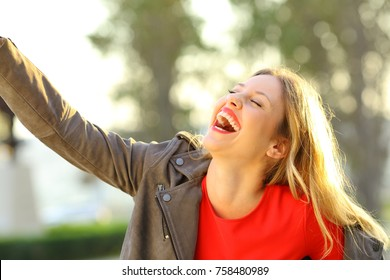 Funny fashion woman laughing and joking outdoors in a park