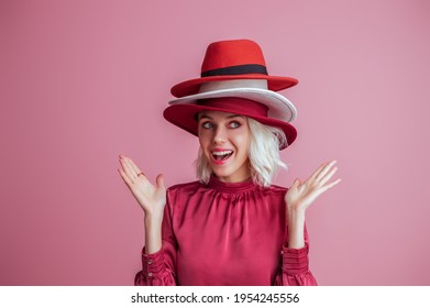 Funny fashionable woman wearing three hats, posing on pink background. Model looking up. Fashion, sale, shopping advertising conception. Copy, empty space for text