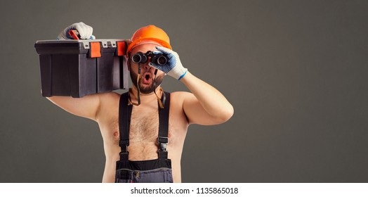 Funny fat bearded builder with binoculars.