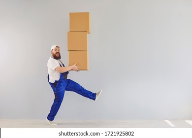 Funny fat bearded delivery courier loader man in a blue uniform with a cardboard box on a gray background.