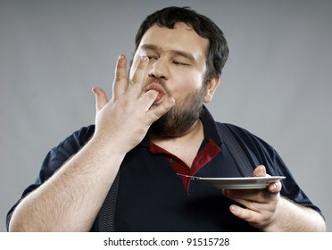 funny fat bearded man eating chocolate cake. He is wearing a dark blue polo and pants with suspenders. In the hands of a teaspoon and a dish. Photo taken in a studio.