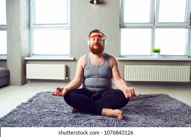 A funny fat bearded man in the headphones does yoga.