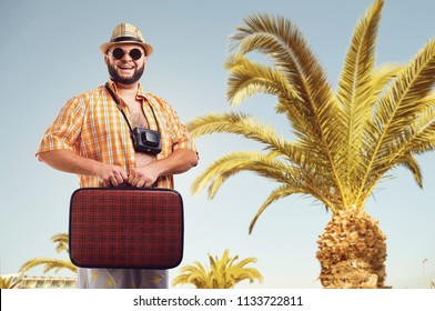 Funny fat bearded man with a suitcase on vacation.