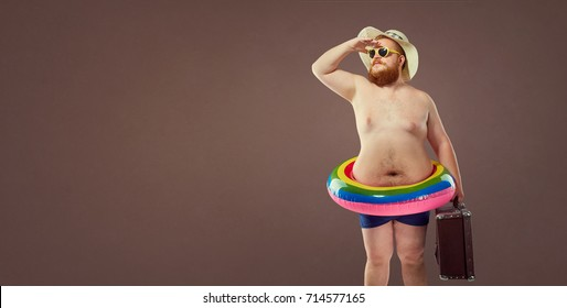 Funny fat bearded man with a suitcase in a hat and glasses on va