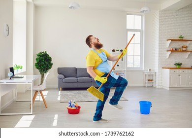 Funny fat man with a beard in an apron dancing cleans the room in the house.