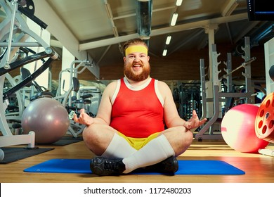 Funny fat man with a beard doing yoga in the gym