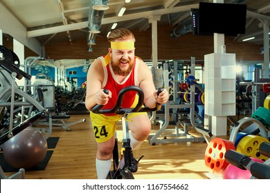 A funny fat man  doing exercises on an exercise bike in a sports