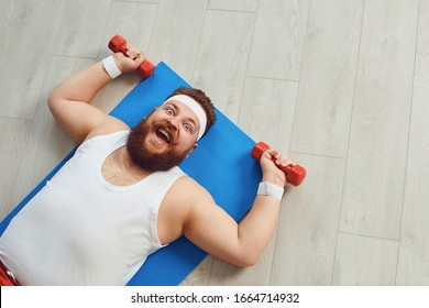 Funny fat man doing exercises with dumbbells on a workout on the floor in the house.