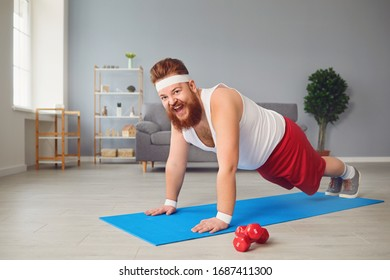 Funny fat man doing exercises on the floor smiling on the floor at home.