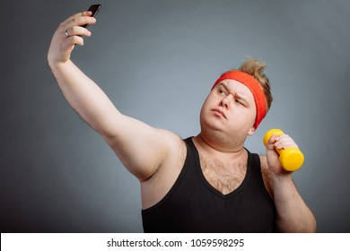 Funny fat man with duck lips wearing black shirt with big belly, holding dumbbell, doing selfie on grey background