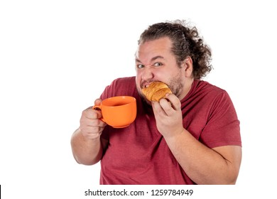 Funny fat man eating small croissant and drinking coffee from big orange cup on white background. Good morning and breakfast