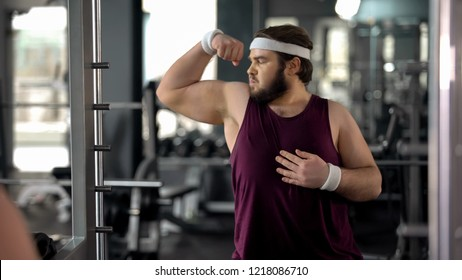 Funny fat man looking at mirror reflection gym and posing, pretending muscular