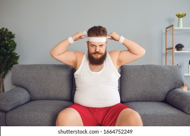 Funny fat man in sportswear is sitting on the sofa in the room