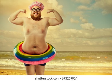Funny fat man in a swimsuit with an inflatable circle on the bea