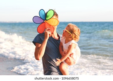 Funny father and cute daughter having fun playing on the beach at sunset. Family,colour, vacation concept.