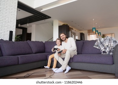 Funny father and little preschool son playing video games sitting on couch in living room at home, holding joypad, having fun with new technology console online. Weekend, free time with family concept