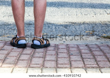 Funny feet covered with socks and sandals