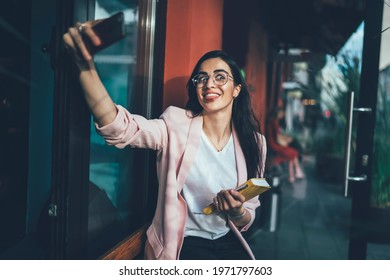 Funny female author poet with textbook for creating using cellphone front camera for clicking selfie pictures during break, joyful Georgian woman in glasses shooting positive video in sidewalk