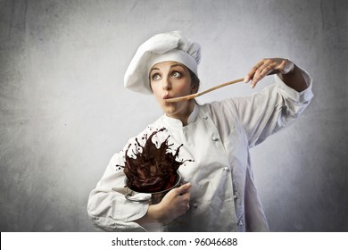 Funny female cook tasting some chocolate dough spilling from a pot