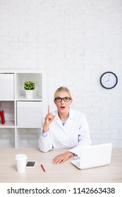 funny female doctor or scientist showing idea sign in office - copy space over white brick wall