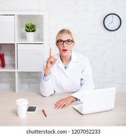 funny female doctor or scientist showing idea sign in modern office