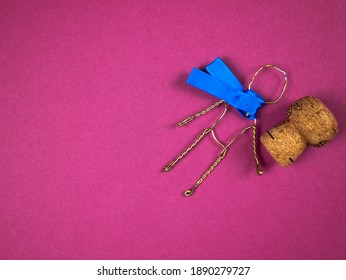 Funny figure of person made of muselet with champaign cork on the pink background