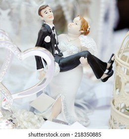 Funny figurines bride and groom on top of wedding cake