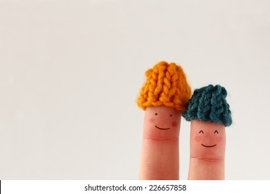 Funny finger people couple smiling with red cheeks wearing knitted woolen hats