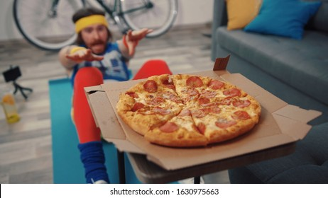 Funny fitness man doing abdominal crunches exercise failing to reach tasty hot pizza in the living room at home.