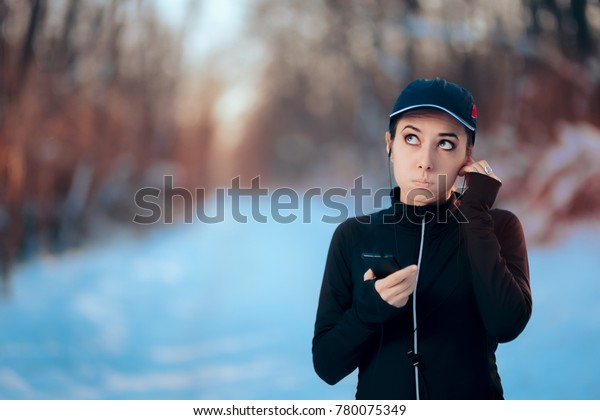 Funny Fitness Woman Listening to Music on Her Smartphone. Girl with earphones and checking her phone