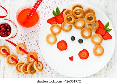Funny food art idea for healthy baby girl breakfast - bagels with berry in the form of smiling face. Picture on a plate, fun with food concept