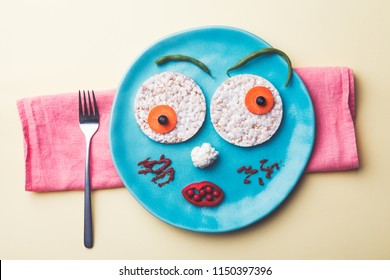 funny food face made of tasty fresh colorful vegetables and bread crisps, creative kids breakfast, top view