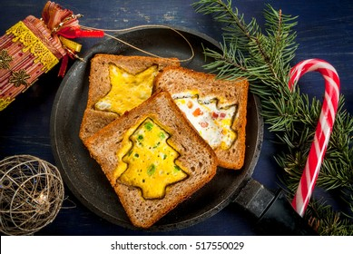 Funny food for kids, Christmas breakfast: toast with scrambled eggs in the shape of Christmas trees and stars, on dark blue festive table with fir branches and decorations, top view, copy space