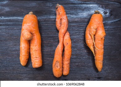 Funny forms of carrots on background of dark board.