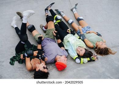 Funny four skaters chilling on a quarter pipe legs up at skatepark. Wearing some protective gear. Talking to each other.