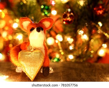 Funny fox with herart. New years greetings background. Fancy handmade toy from wool on bokeh Christmas background. Place for insert logo or write text. Copyspace for congratulations.
