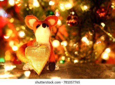 Funny fox. New years greetings background. Fancy handmade toy from wool on bokeh Christmas background. Place for insert logo or write text. Copyspace for congratulations.