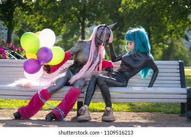 funny freaks, dressed in a unicorn bright costume and anime face mask with latex catsuit, enjoy life in the city Park