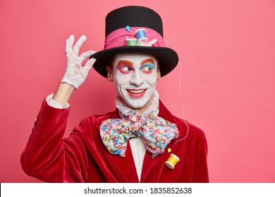 Funny friendly positive hatter keeps hand on hat looks away with smile dressed in costume with big bowtie entertains people on halloween party poses indoor against pink background. Happy circus actor