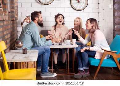 So funny! Friends in cafe having fun, laughing, drinking coffee and enjoying their time. Lifestyle and friendship concepts
