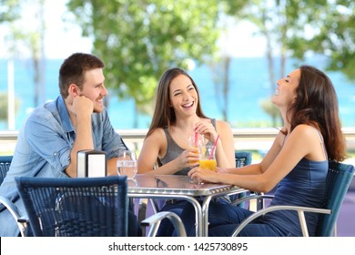 Funny friends talking and laughing in a coffee shop or hotel on the beach on vacation