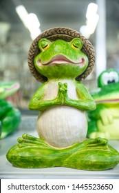 Funny frog figurine in yoga pose, meditation