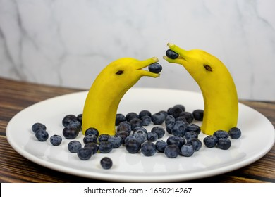 funny fruit figure two banana dolphins with blueberries on a white plate