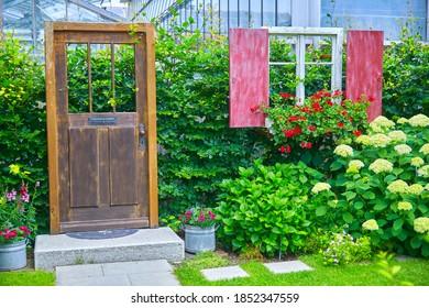 Schöne Gartendekoration mit Tür- und Fensterpuppe.