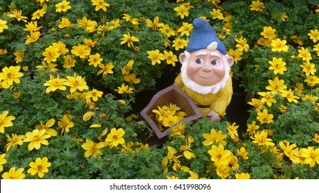 Funny garden gnome  in the flower bed