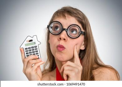 Funny geek or nerd school woman with calculator in her hand
