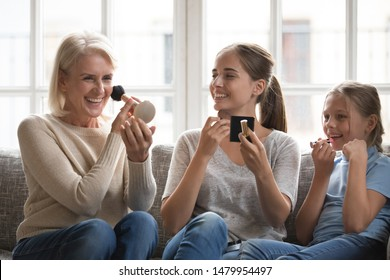Funny girl applying pink lipstick imitating copying young mother and elderly grandmother three pretty female diverse generations sit on couch at home having fun using beauty products teach little kid