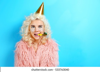 Funny girl in birthday hat on blue background