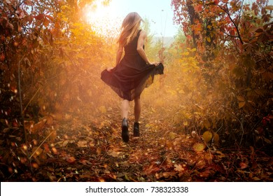 funny girl in black dress running in golden autum forest